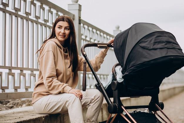 公園のベビーカーで歩く若い母親 無料写真