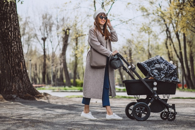 Young mother walking with baby carriage in park Free Photo