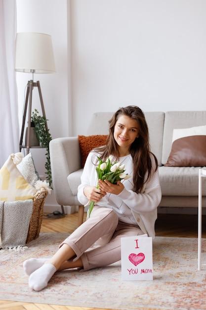 튤립 꽃다발과 거실에서 엽서와 함께 젊은 어머니 프리미엄 사진
