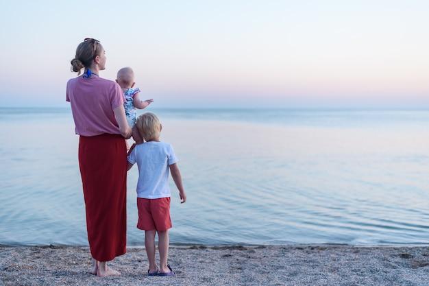 Молодая мать с ребенком и старший сын стоять на берегу моря. вид сзади семья на пляже на закате Premium Фотографии