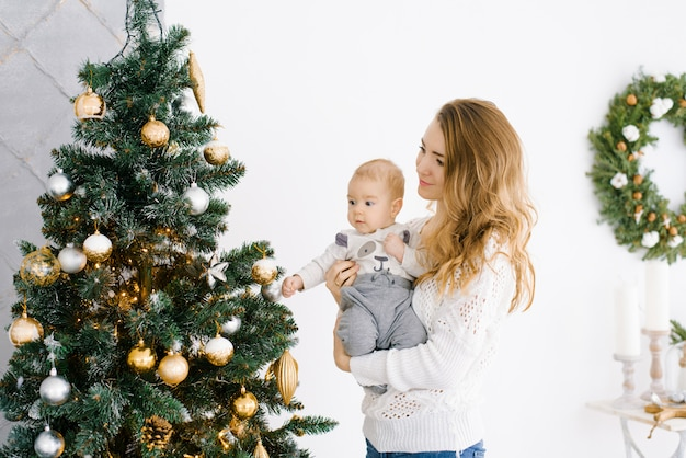 A young mother with blonde hair holds her little son in her arms, they are happily celebrating christmas and new year Premium Photo