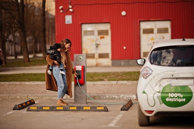 電気ガソリンスタンドで電気自動車を充電する子供を持つ若い母親。 Premium写真