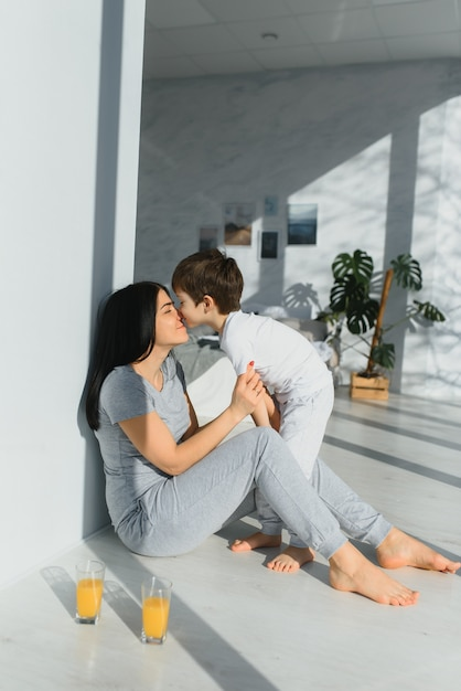 Young mother with her 6 years old little son dressed in pajamas are relaxing and playing in the bed Premium Photo