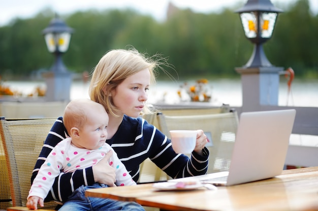 Young mother with her adorable baby girl working or studying on laptop in outdoor cafe Premium Photo