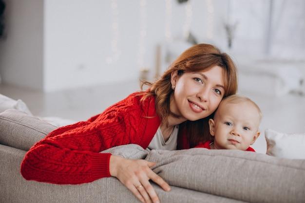 소파에 앉아 그녀의 아기 아들과 젊은 어머니 무료 사진