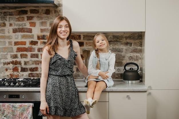 부엌에서 그녀의 귀여운 딸과 함께 젊은 어머니 프리미엄 사진