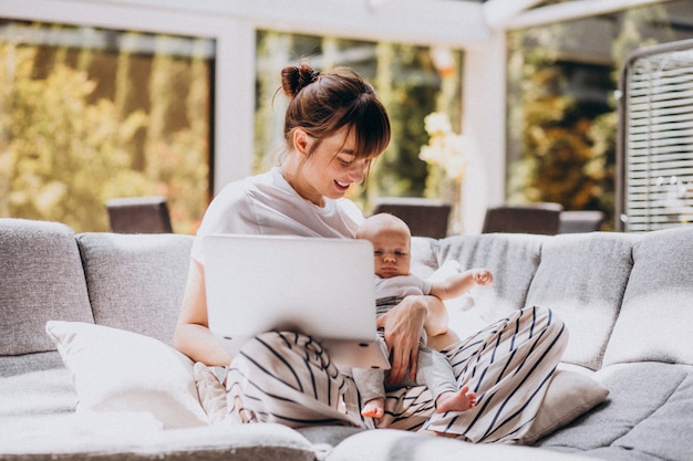 Young mother with her kid working at home on a computer Free Photo