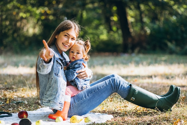 Young mother with her little daughter in an autumn park having picnic Free Photo