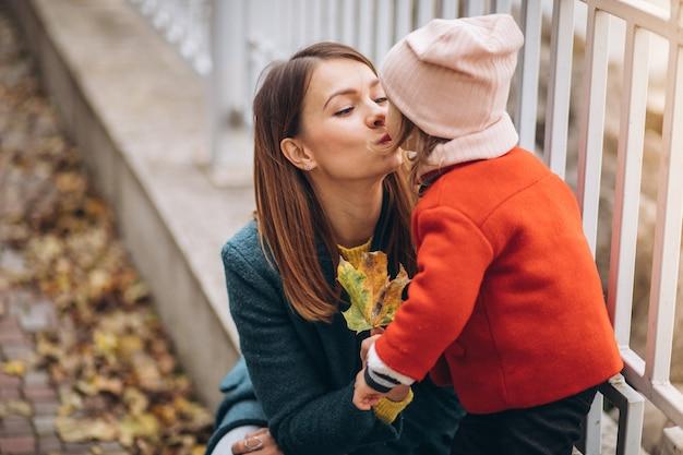 秋の公園で幼い娘と若い母親 無料写真