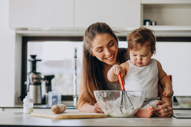 Young mother with her little son cooking at kitchen Free Photo