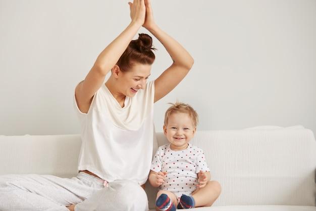 Молодая мать с годовалым маленьким сыном, одетые в пижаму, расслабляются и играют Бесплатные Фотографии