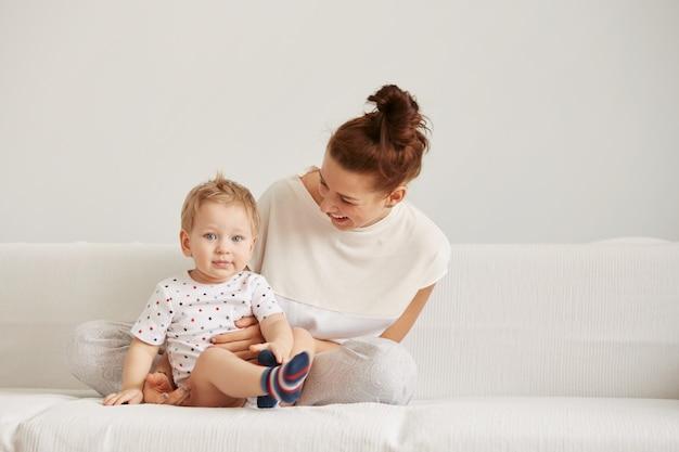 La giovane madre con il suo piccolo figlio di un anno vestito in pigiama sta rilassando Foto Gratuite