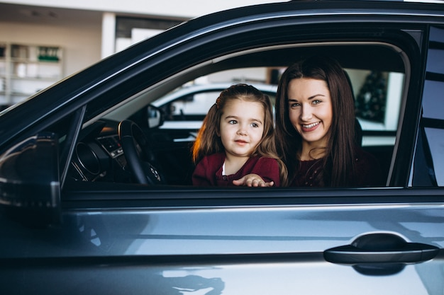 Young mother with little daughter sitting inside a car Free Photo