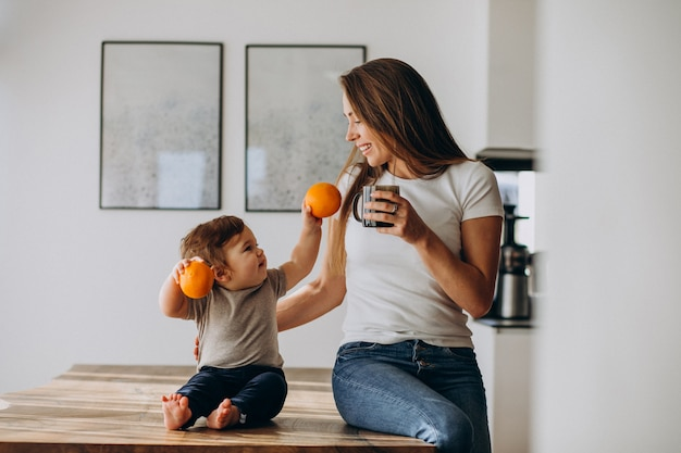 Young mother with little son drinking water at home Free Photo