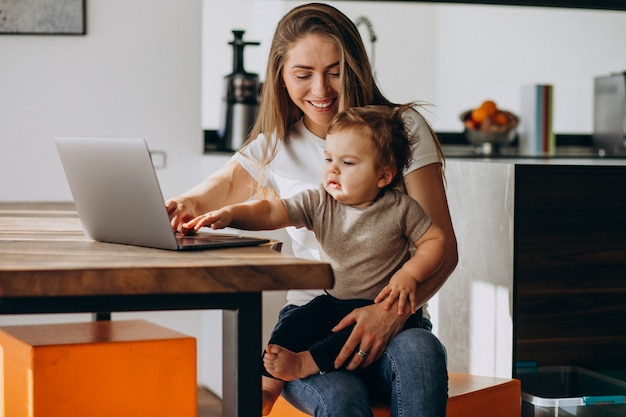 Young mother working from home on laptop with her little son Free Photo