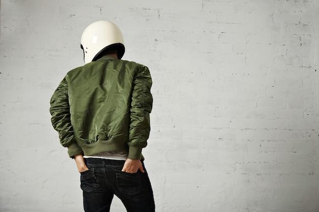 흰색 벽과 그의 청바지 뒷 주머니에 그의 손으로 뒤에서 흰색 헬멧과 녹색 재킷 초상화에 젊은 오토바이. 무료 사진