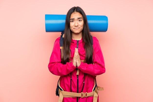 Индийская девушка молодой альпинист с большим рюкзаком изолирована на розовой мольбе Premium Фотографии