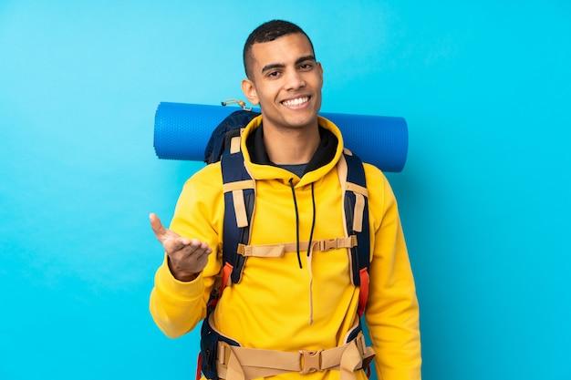かなりの後に孤立した青いウォールハンドシェーク上の大きなバックパックを持つ若い登山家男 Premium写真