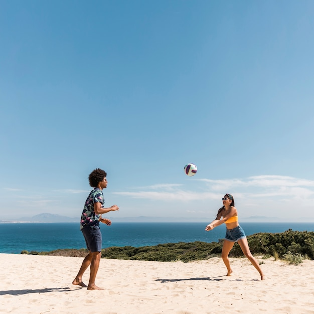 Young multicultural couple playing volleyball on beach Free Photo