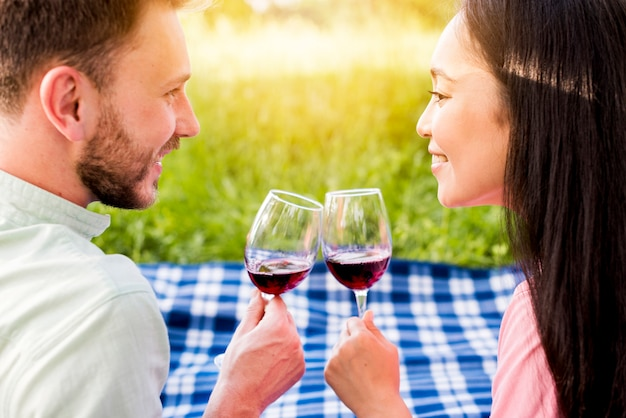 Young multiethnic enamored couple drinking red wine on picnic Free Photo