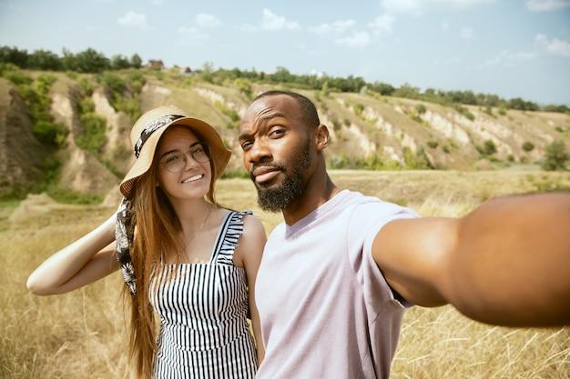 晴れた夏の日の牧草地で屋外の若い多民族の国際的なカップル。一緒にピクニックをしているアフリカ系アメリカ人の男性と白人女性。関係の概念、夏。自撮り写真を作る。 無料写真