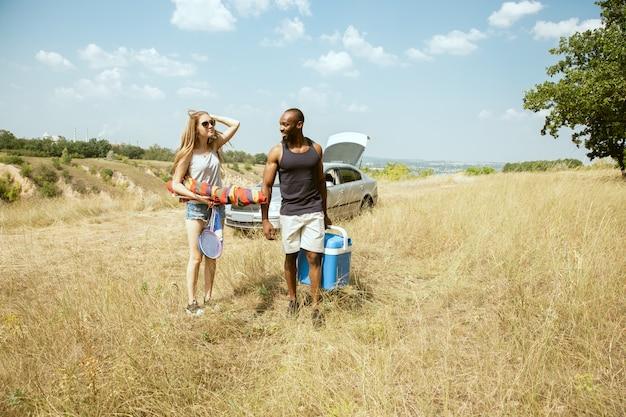晴れた夏の日の牧草地で屋外で若い多民族の国際的なロマンチックなカップル。一緒にピクニックをしているアフリカ系アメリカ人の男性と白人女性。関係の概念、夏。 無料写真