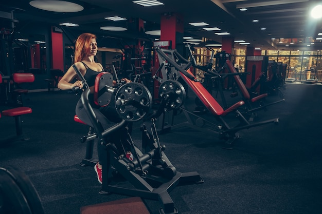 Young muscular caucasian woman practicing in gym with equipment. wellness, healthy lifestyle, bodybuilding. Free Photo