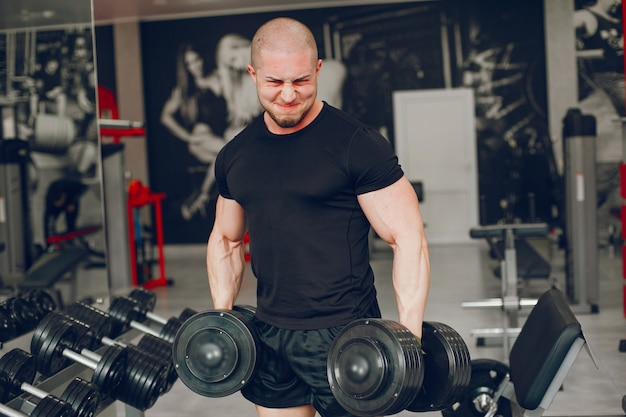 A young and muscular guy in a black t-shirt trains in a gym Free Photo