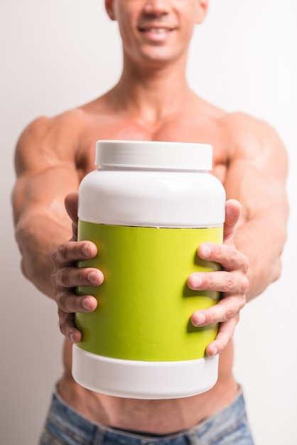 Young muscular man with jar of protein. Premium Photo