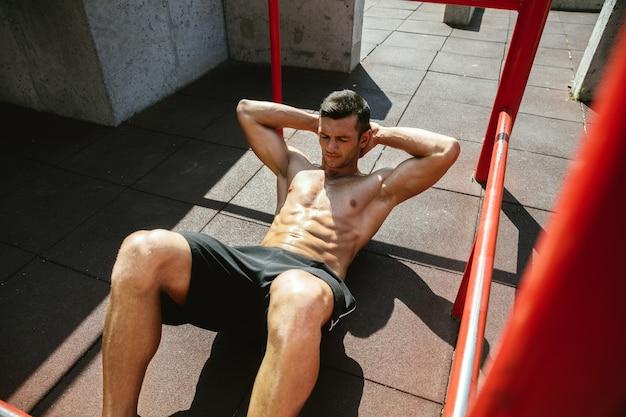Giovane uomo caucasico senza camicia muscolare che fa gli scricchiolii sulla barra orizzontale al parco giochi nella soleggiata giornata estiva. allenamento della parte superiore del corpo all'aperto. concetto di sport, allenamento, stile di vita sano, benessere. Foto Gratuite