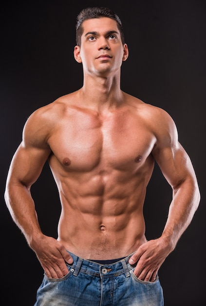 Young muscular shirtless man has his hands in his pockets. Premium Photo