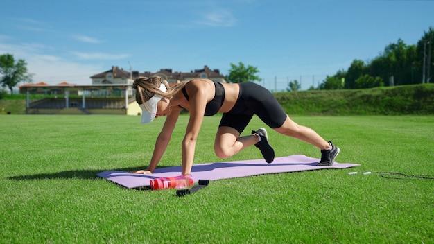 晴れた夏の日にマットの上で登山運動をしている白い帽子をかぶった若い筋肉の女性。新鮮な緑の芝生のスタジアムフィールドでコア筋肉をトレーニングするゴージャスな女の子。トレーニングの概念。 Premium写真