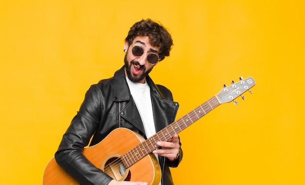 ギター、ロックンロールのコンセプトで予想外の何かを見て、愚かで驚いた表情で困惑し、混乱している若いミュージシャンの男性 Premium写真