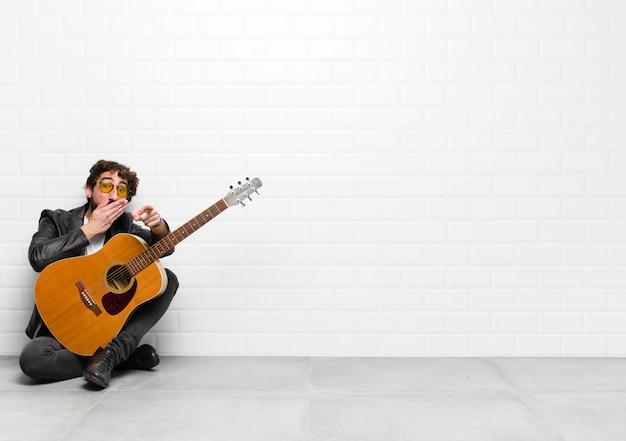 若いミュージシャン男があなたを笑って、からかったり、ギター、ロックンロールのコンセプトであなたをからかう Premium写真