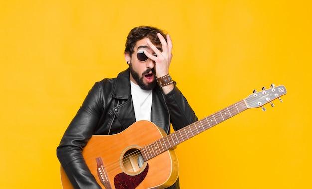 ショック、怖い、または恐怖を探している若いミュージシャン男の手で顔を覆っているとギター、ロックンロールのコンセプトで指の間を覗く Premium写真