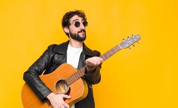 フレンドリーで自信を持って、前向きな表情で幸せそうに笑って、提供し、オブジェクトまたはコンセプトをギター、ロックンロールのコンセプトで示す若いミュージシャン男 Premium写真