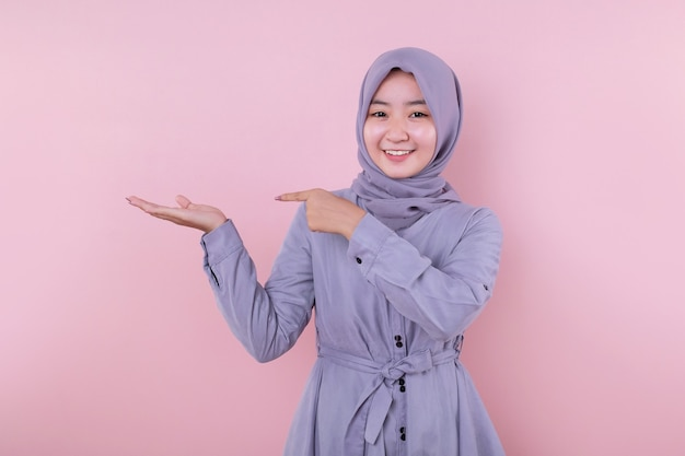 Young muslim girl pointing a hand and smile cheerful Premium Photo