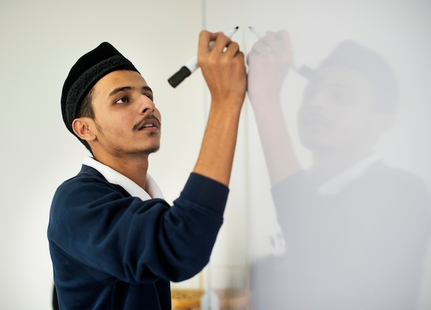 Young muslim man is writing a white board Free Photo