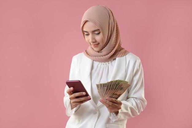 Молодая мусульманка держит деньги и смартфон Premium Фотографии