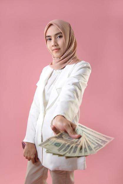 Молодая мусульманка держит деньги Premium Фотографии