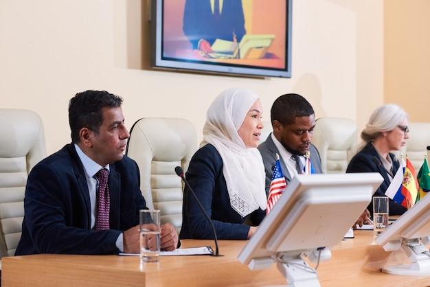 外国の同僚の間でビジネスや政治会議でスピーチをする白いヒジャーブの若いイスラム教徒の女性 Premium写真