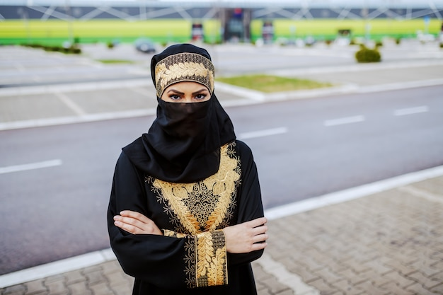 Young muslim woman in traditional wear standing outdoors with arms crossed. Premium Photo