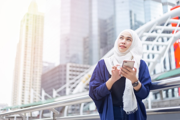 Young muslim woman using smartphone. looking to sky Premium Photo