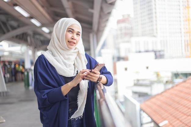 Young muslim woman using telephone on skytrain station. Premium Photo