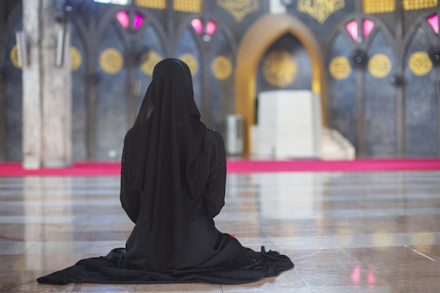 Young muslim woman in wear black dress sitting alone in mosque, rear view. Premium Photo