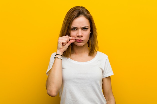 Young natural caucasian woman with fingers on lips keeping a secret. Premium Photo