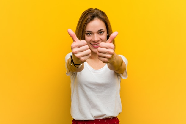 Young natural caucasian woman with thumbs ups, cheers about something, support and respect concept. Premium Photo