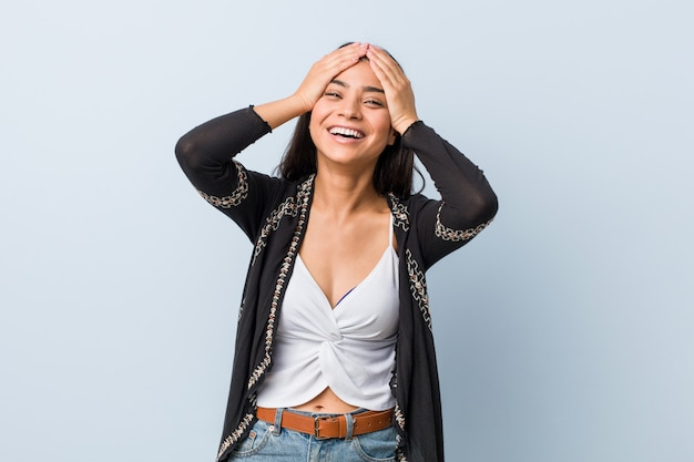 Young natural and pretty arab woman laughs joyfully keeping hands on head. happiness . Premium Photo