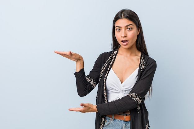 Young natural and pretty arab woman shocked and amazed holding a copy space between hands. Premium Photo