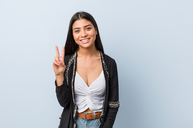 Young natural and pretty arab woman showing victory sign and smiling broadly. Premium Photo